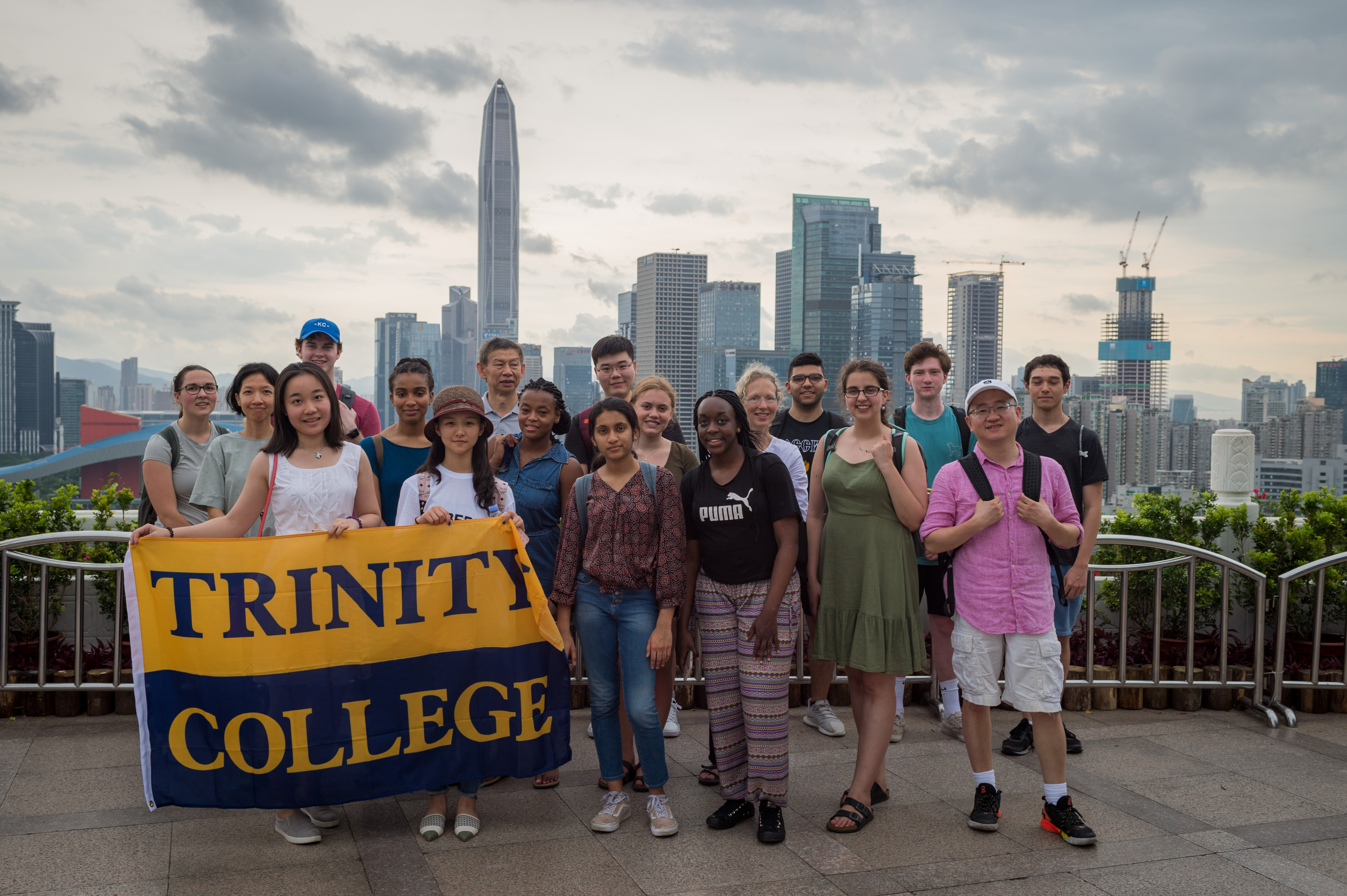 Students and faculty stand in front of the Shenzhen skyline